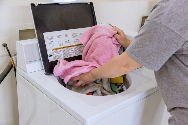 Mulher colocando toalha, o aparelho da máquina de lavar é detergente para a roupa