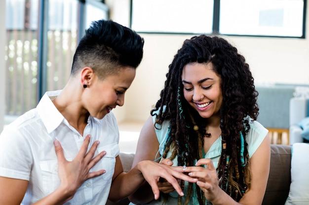 Mulher colocando um anel surpresa no dedo parceiros
