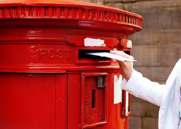 Mulher colocando um cartão na caixa de correio vermelha e andando pela cidade inglesa