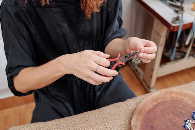 Mulher colocando um gancho francês no brinco