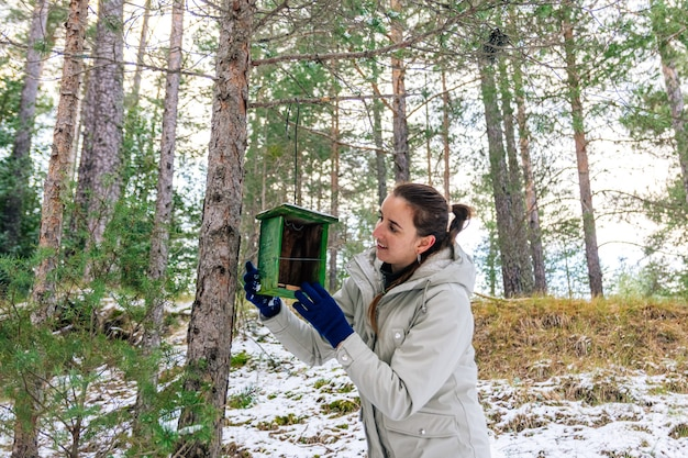 Mulher colocando um ninho de pássaro de madeira na floresta. paisagem de neve