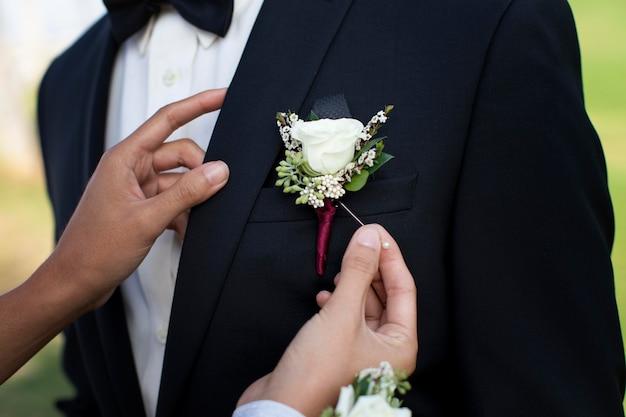 Mulher colocando uma flor no terno do namorado para o baile