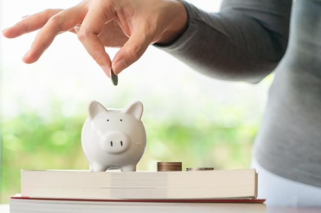 Mulher colocando uma moeda para salvar o cofrinho, economizando dinheiro para o conceito de educação