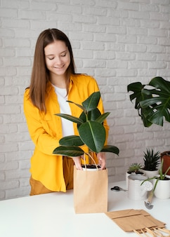 Mulher colocando uma planta em um saco de papel