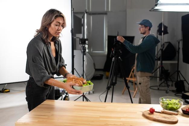 Mulher colocando uma tigela de comida para a equipe de cinema