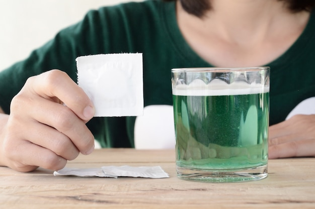 Mulher colocar comprimido efervescente em copo de água na mesa de madeira