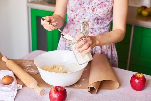Mulher colocar ingredientes para torta de maçã em uma tigela grande branca. preparando massa na cozinha