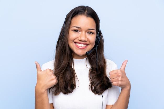 Mulher colombiana de telemarketing jovem sobre parede azul isolada, dando um polegar para cima gesto