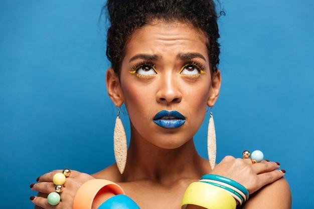 Mulher colorida emocionada de raça mista com maquiagem da moda e acessórios, olhando para cima com as mãos cruzadas nos ombros, parede azul