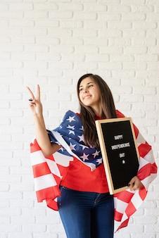 Mulher com a bandeira americana segurando o quadro de cartas com as palavras feliz dia da independência e mostrando o cartaz