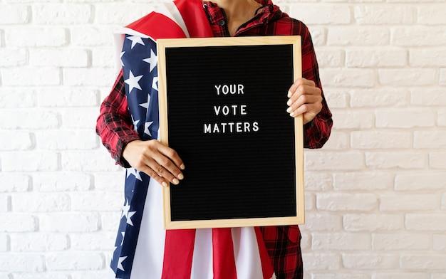 Mulher com a bandeira americana segurando um quadro de correspondência com o texto your vote matters em fundo de tijolo branco