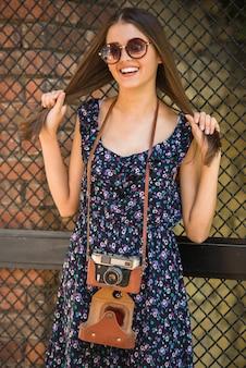 Mulher com a câmera antiquado que está ao ar livre.