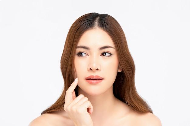 Mulher com a mão a tocar no rosto para conceitos de beleza e cuidados com a pele