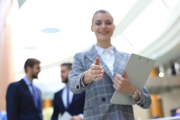 Mulher com a mão aberta pronta para um aperto de mão no escritório.