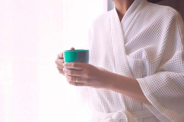 Mulher com a mão da roupa de noite que guarda o copo de café.