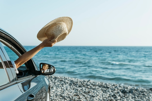 Mulher com a mão na janela do carro segurando um chapéu perto do mar