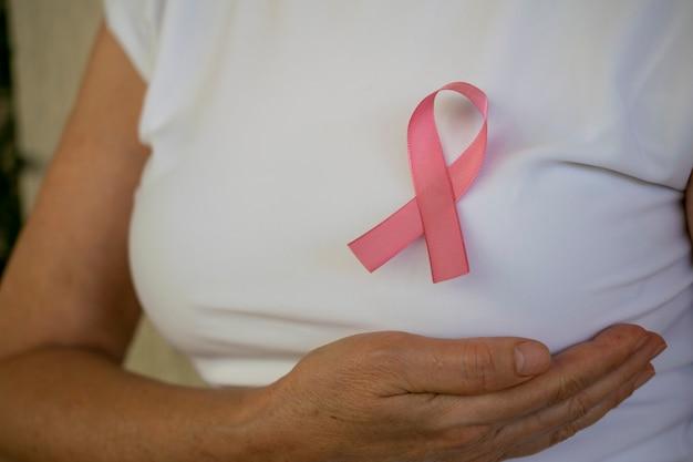 Mulher com a mão no peito e laço rosa na camiseta campanha de prevenção do câncer de mama outubro rosa