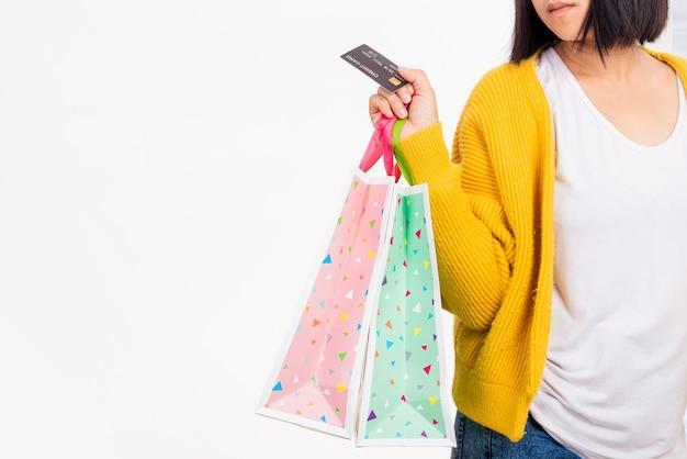 Mulher com a mão segurando sacolas multicoloridas e cartão de crédito