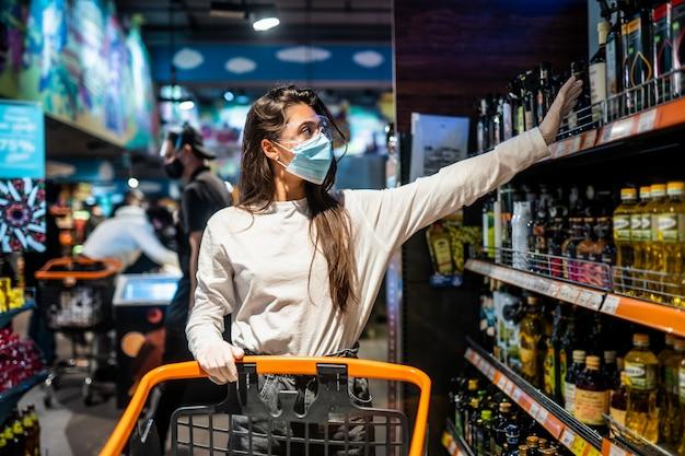 Mulher com a máscara cirúrgica e as luvas está fazendo compras no supermercado após a pandemia do coronavírus. a menina com máscara cirúrgica vai comprar a comida.