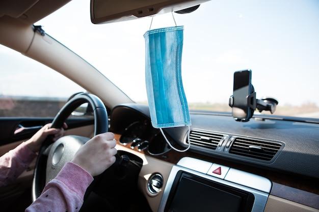 Mulher com a máscara médica no carro. coronavírus, doença, infecção, quarentena, covid-19