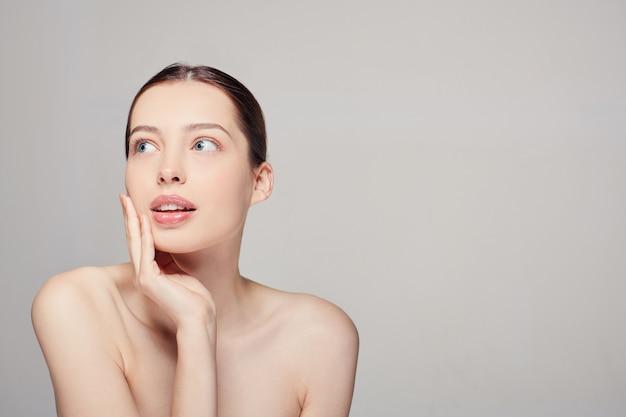 Mulher com a pele limpa, fresca, olhos azuis, cabelos escuros e maquiagem nude