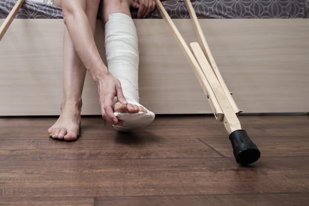 Mulher com a perna quebrada sentada na cama segurando muletas e tocando a perna quebrada