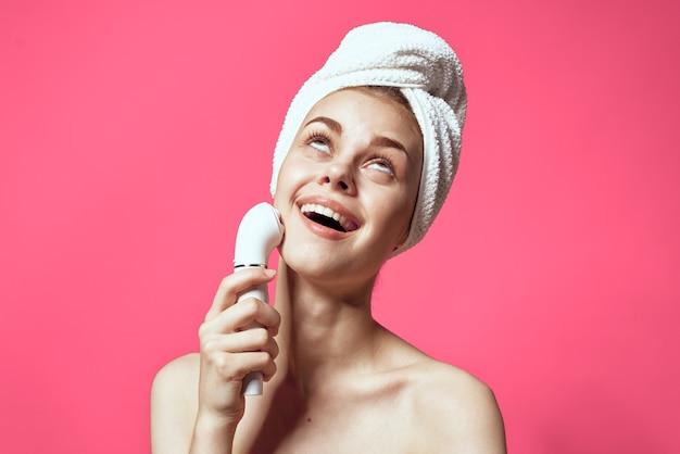 Mulher com a toalha na cabeça limpando a pele dos ombros nus fundo rosa