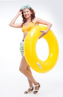 Mulher com acessórios de natação em fundo branco