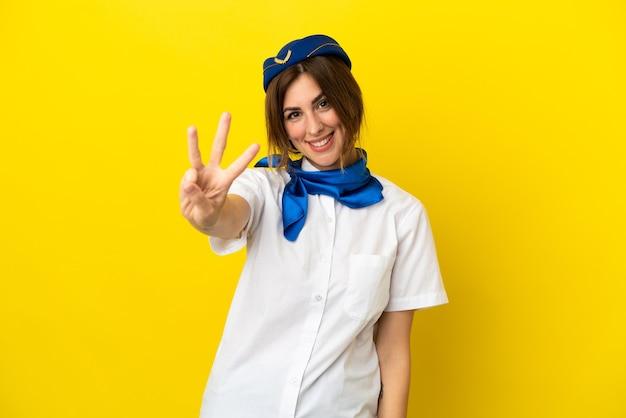 Mulher com aeromoça de avião isolada em fundo amarelo feliz e contando três com os dedos