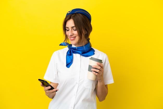 Mulher com aeromoça de avião isolada em um fundo amarelo segurando um café para levar e um celular
