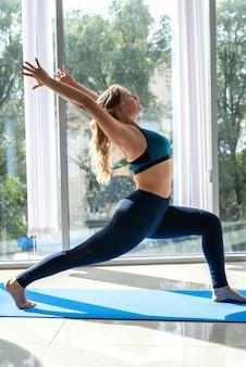 Mulher com agasalho fazendo exercícios de dor lombar, fitness de reabilitação. conceito de saúde