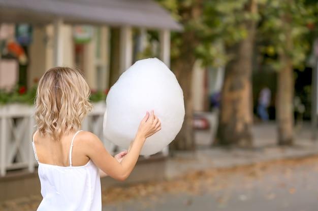 Mulher com algodão doce doce ao ar livre
