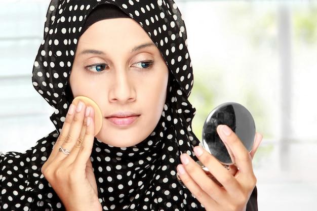 Mulher com almofada de algodão, aplicar pó facial