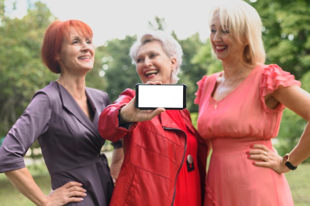 Mulher com amigos, segurando o telefone móvel