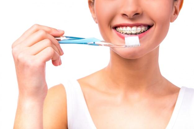 Mulher com aparelho nos dentes, limpa os dentes com escova de dentes.