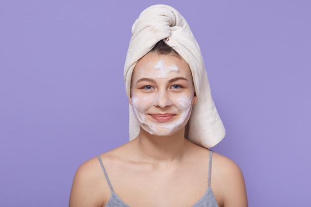 Mulher com aparência agradável, sendo envolvida em toalha branca e máscara facial branca no rosto