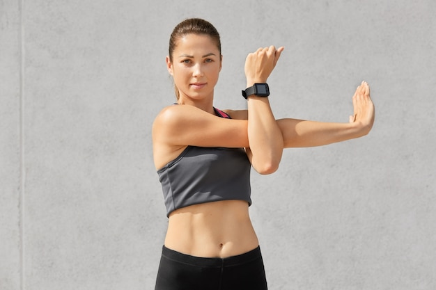 Mulher com aparência atraente, faz exercícios, estica as mãos, usa blusa casual, smartwatch para controlar sua saúde