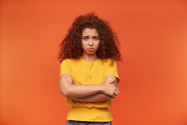 Mulher com aparência chateada, cabelo ruivo cacheado e camiseta amarela