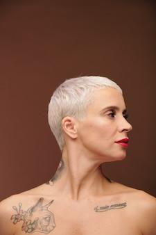 Mulher com aparência de homem com cabelo loiro curto, tatuagens nos ombros, pescoço e tórax e batom vermelho nos lábios mantendo a cabeça virada para o lado em isolamento