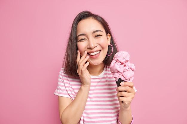 Mulher com aparência oriental sorri com os dentes vestida com uma camiseta listrada casual segurando sorvete de waffle e está de bom humor