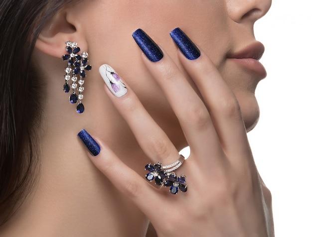 Mulher com arte de unha, promovendo o anel e brincos de luxo de design.