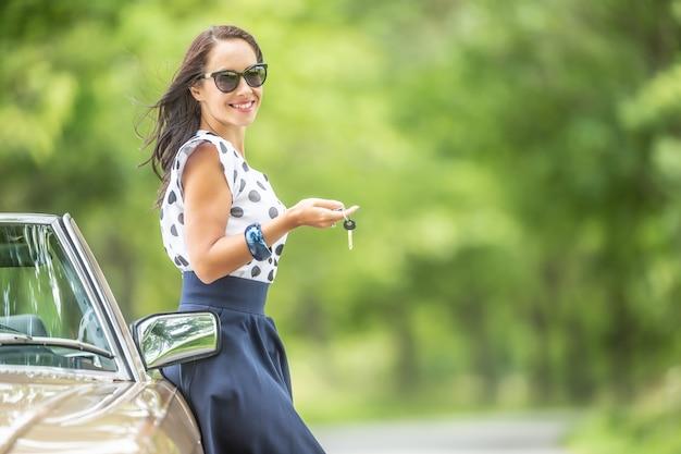Mulher com as chaves do carro na mão se inclina contra um conversível vintage estacionado na natureza.
