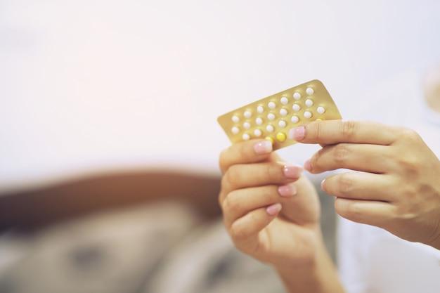 Mulher com as mãos abrindo pílulas anticoncepcionais na mão. comer pílula anticoncepcional.