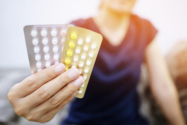 Mulher com as mãos abrindo pílulas anticoncepcionais na mão. tomando pílula anticoncepcional.