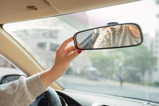 Mulher com as mãos ajustando o espelho retrovisor do carro