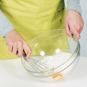Mulher com as mãos batendo a massa na cozinha