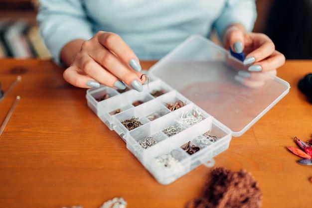 Mulher com as mãos contra a caixa com acessórios para bordado, mestre no trabalho. joias artesanais. artesanato, confecção de bijuterias