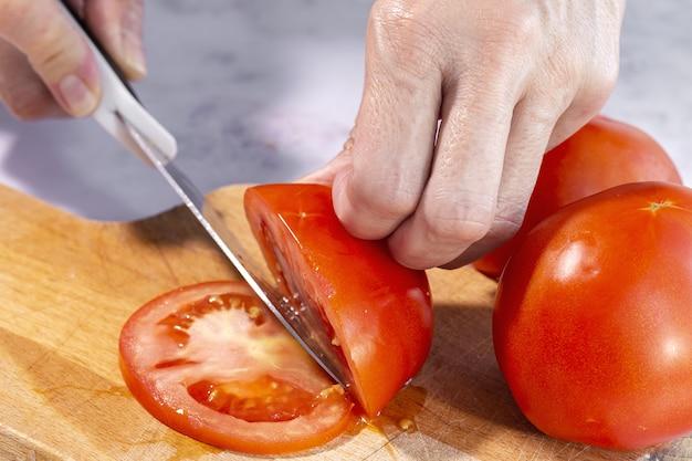 Mulher com as mãos cortando fatias de tomate fresco em uma placa de madeira