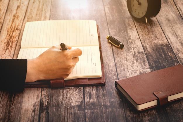 Mulher com as mãos desenhando ou escrevendo, na mesa de madeira.