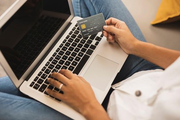 Mulher com as mãos digitando e segurando um cartão de crédito